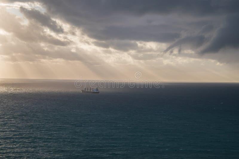 Grande nave di autocisterna sull'oceano liscio con le nuvole di tempesta scure nel cielo I raggi di sole sono striarsi visto attr immagini stock libere da diritti