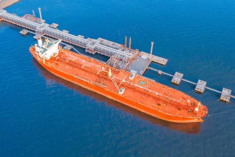 Grande navio petroleiro vermelho, com oleoduto amarrado para carregar produtos petrolíferos e exportar para países distantes atra foto de stock
