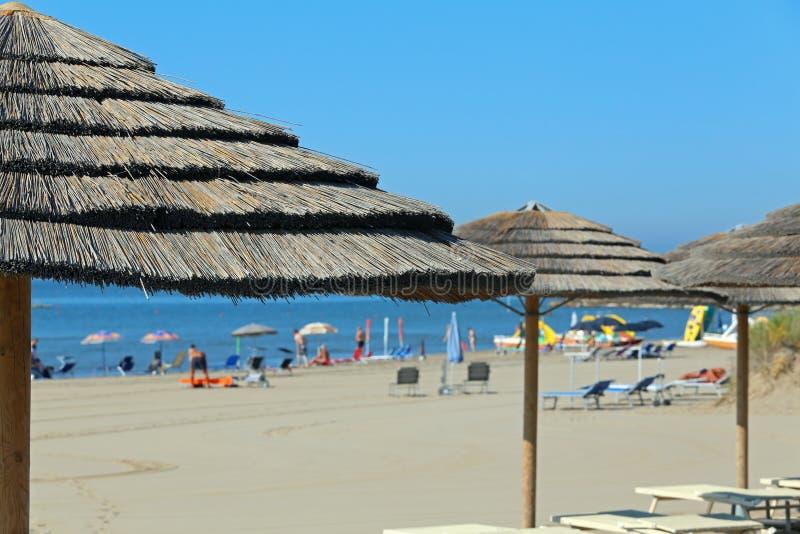 Grande ombrello di spiaggia della paglia da riparare dal sole caldo di estate immagine stock