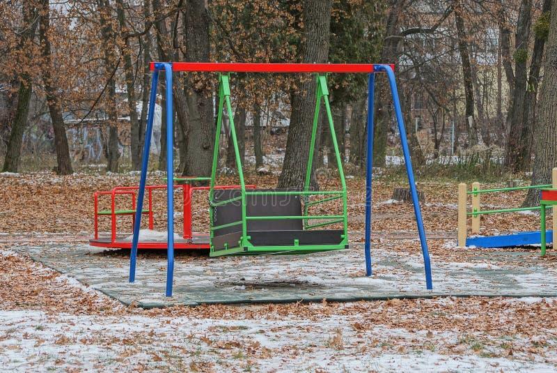 Grande oscillation colorée de fer sur le terrain de jeu en parc d'hiver images stock