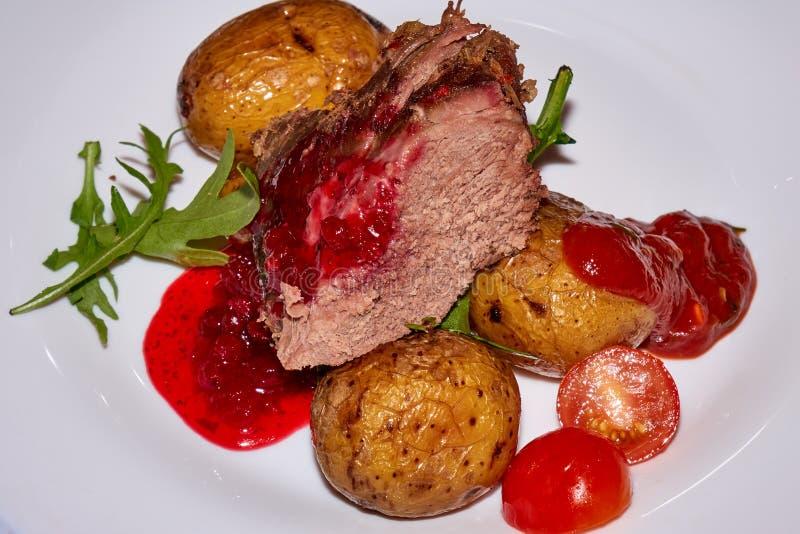 Grande pace della carne arrostita del montone con le patate al forno ed i pomodori freschi fotografie stock libere da diritti