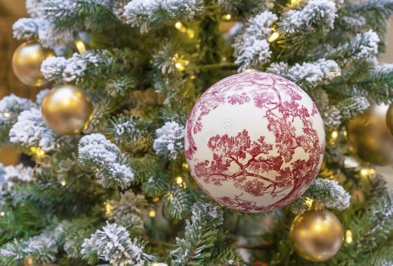 Grande palla con gli ornamenti floreali sull'albero di Natale fotografia stock