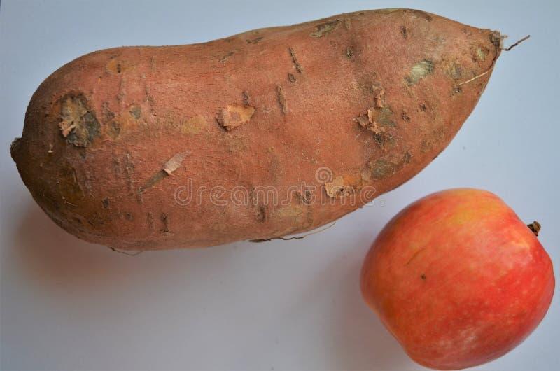 Grande patate douce en comparaison d'une pomme photos libres de droits