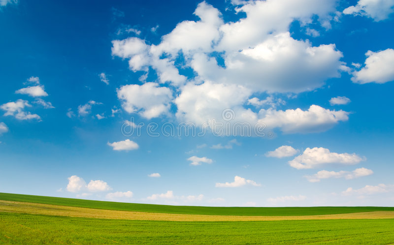 Grande pedaço de terra e céu nebuloso azul fotografia de stock