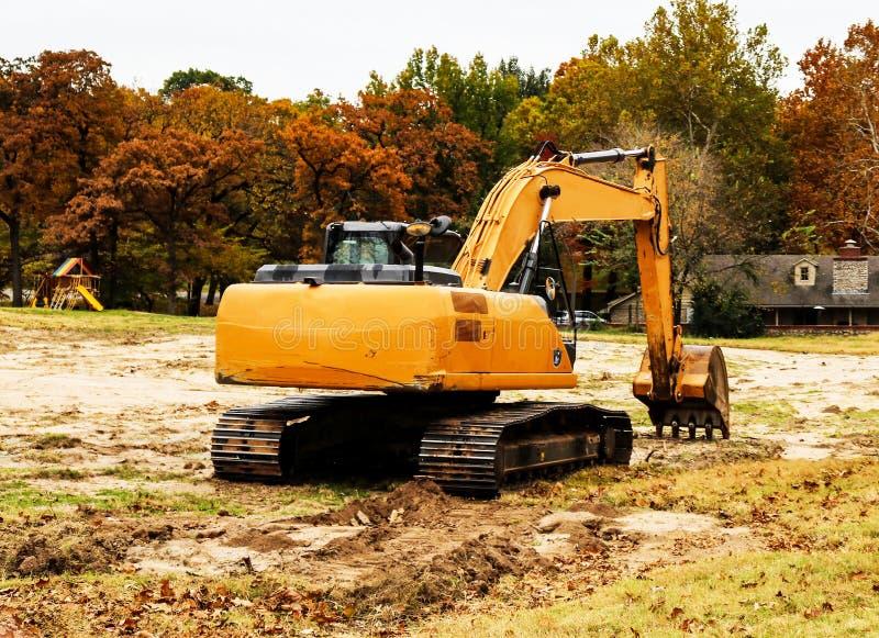 Grande pelle rétro jaune avec des voies se reposant dans le terrain vacant dans la zone résidentielle feuillue avec le swingset g images stock