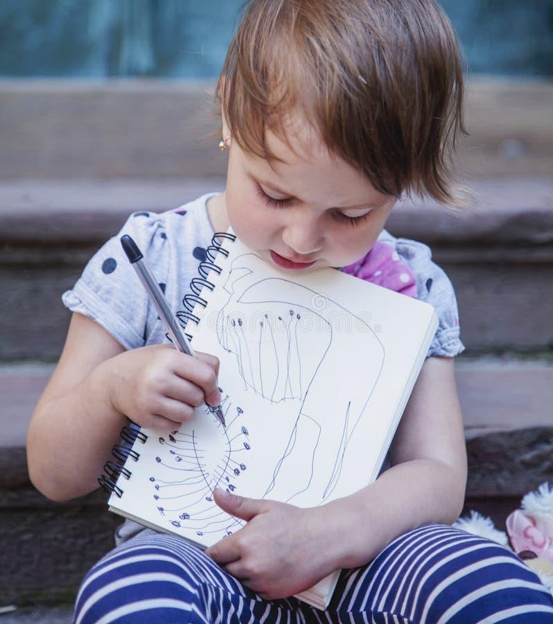Grande photo de Humorous d'artiste de la fille mignonne de petit enfant dessinant a photos stock