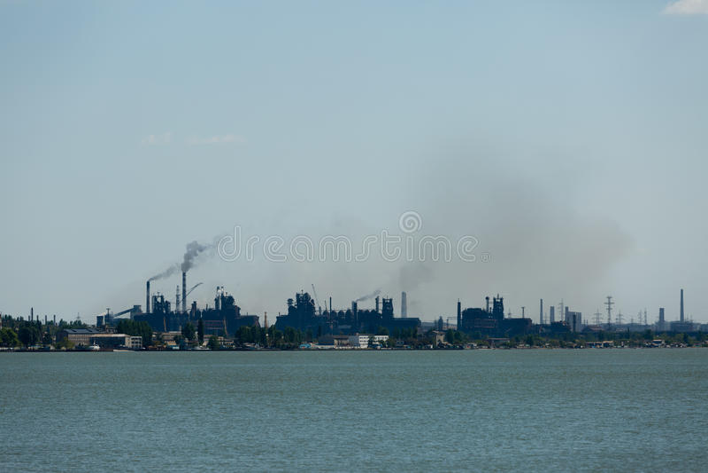 Grande pianta metallurgica della fabbrica d'acciaio con il porto del mare ed i lotti dei tubi che gettano fumo e polvere sporchi  immagine stock libera da diritti