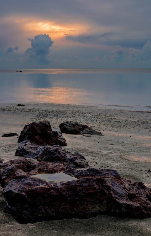 Grande pierre rouge près de la mer au beau lever de soleil de crépuscule images stock