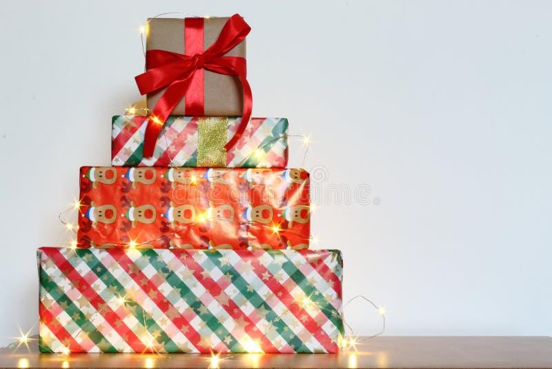 Grande pile des boîte-cadeau enveloppés colorés d'isolement sur la table en bois et le fond blanc Cadeaux de montagne image stock