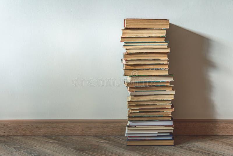 Grande pilha de livros antigos sobre a parede branca imagens de stock royalty free