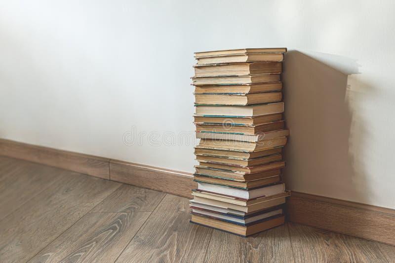 Grande pilha de livros antigos sobre a parede branca foto de stock