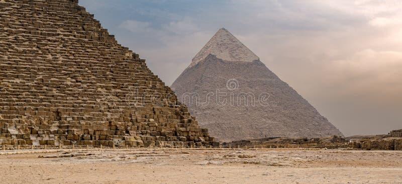 Grande pirâmide de Khufu e pirâmide de Khafre na distância distante com o fundo situado no governo de Giza, o Cairo do céu nebulo imagem de stock