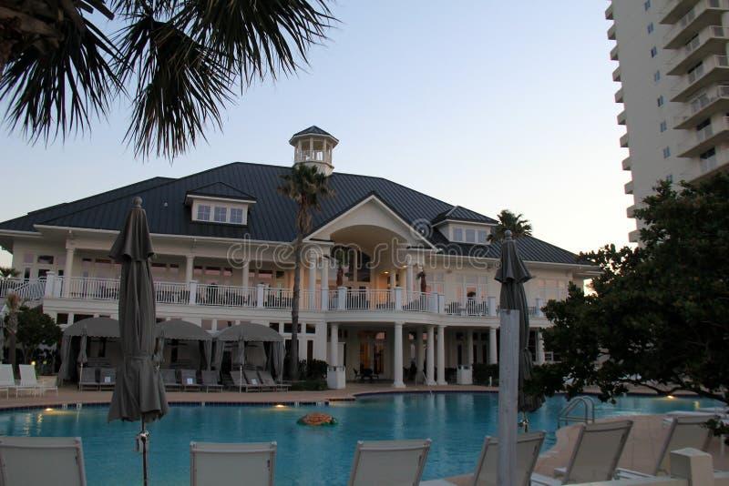 Grande piscine garnie des chaises longues en soleil de début de la matinée, station de vacances de club de plage, rivages de Golf image libre de droits