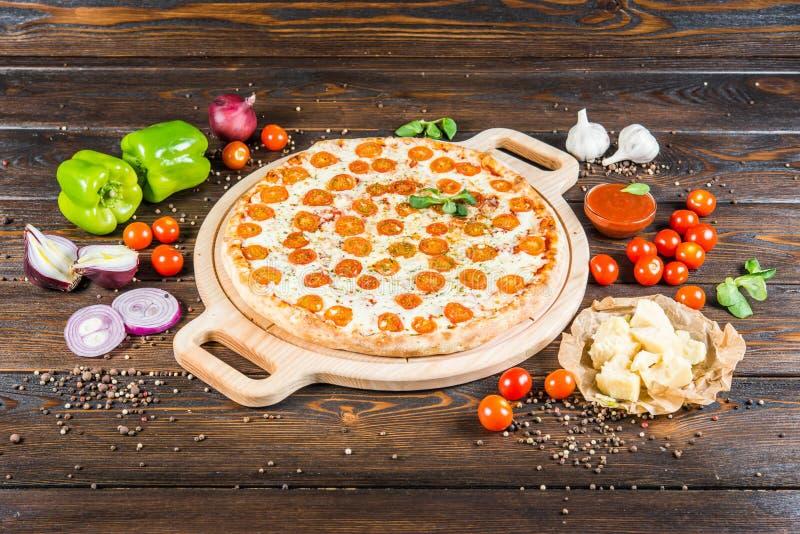 """Grande pizza """"margarita """"avec la planche à découper ronde de fromage et de tomates sur un fond en bois foncé ingrédients photo stock"""