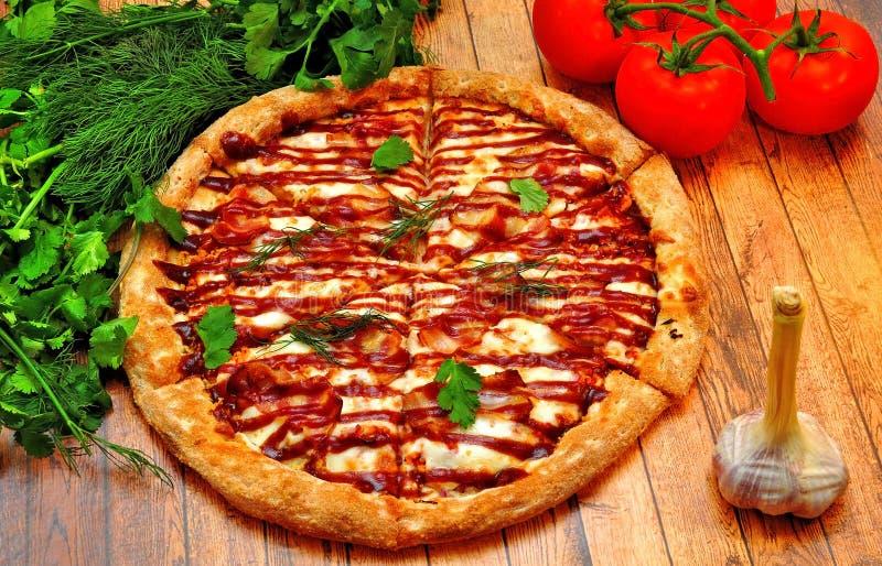 Grande pizza avec un barbecue sur une table en bois image libre de droits