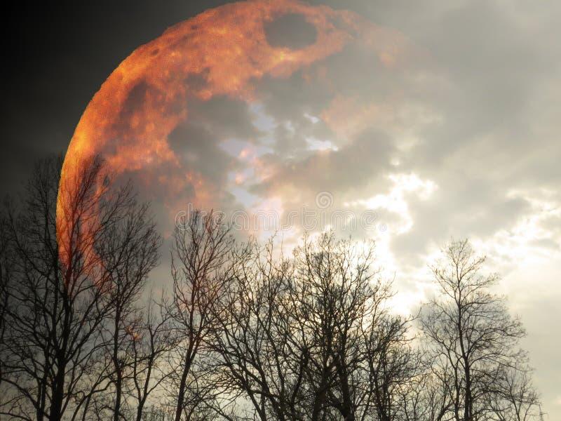 Grande planeta amarelo vivo a arder no céu negro nublado a aparecer atrás de silhuetas florestais e nuvens cinzentas imagem de stock