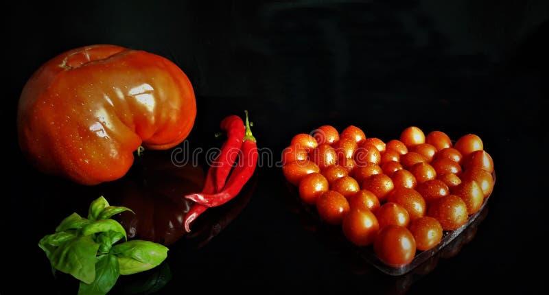 Grande pomodoro rosso, pomodori ciliegia e peperoncino rosso con lo spazio della copia su fondo nero fotografia stock libera da diritti