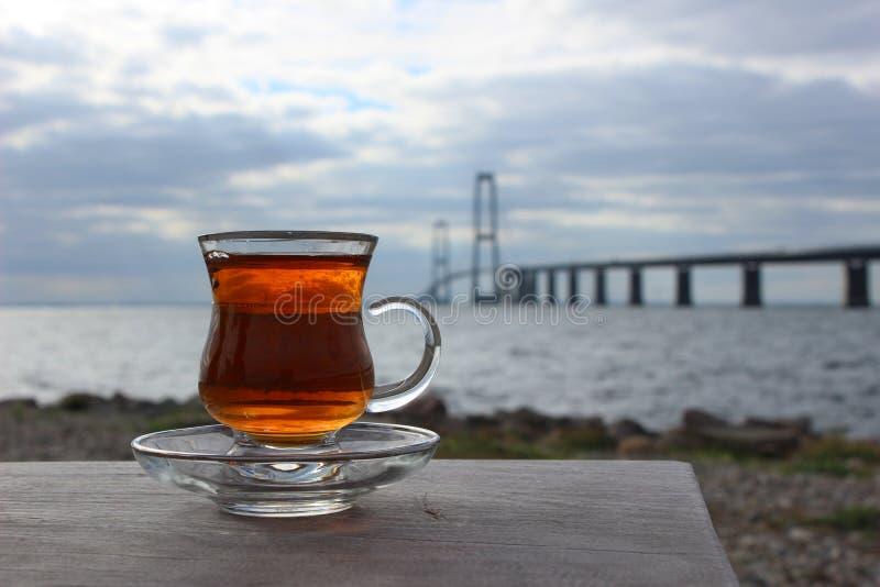 Grande ponte danese della cinghia e tè caldo Foto del ponte e del paesaggio Glas di tè caldo Ponte e bevanda immagini stock libere da diritti
