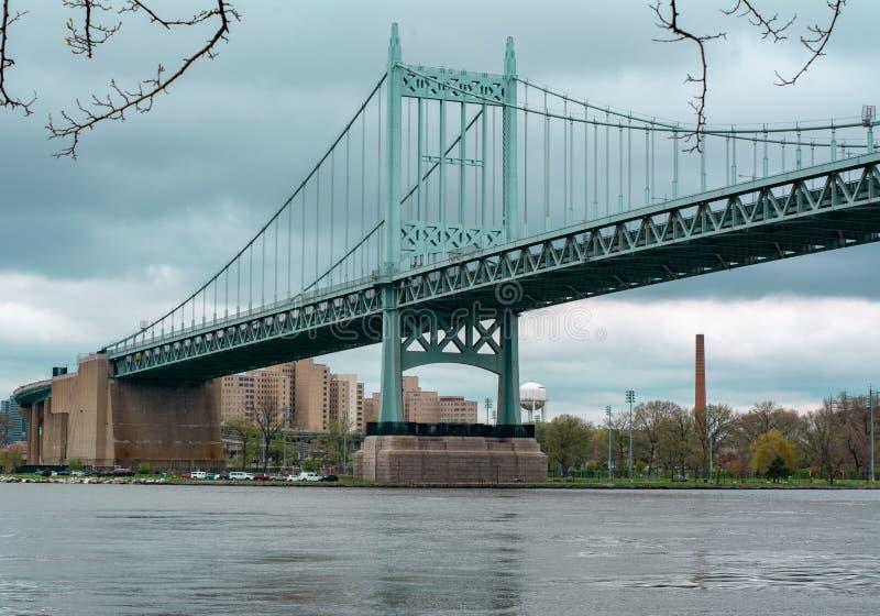 Grande ponte sopra acqua con gli alberi e costruzione nella distanza al parco di Astoria in regine fotografie stock