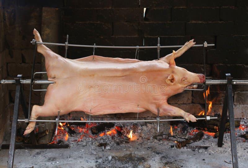 grande porco colado que cozinha lentamente no cuspe de aço no gigantesco foto de stock royalty free
