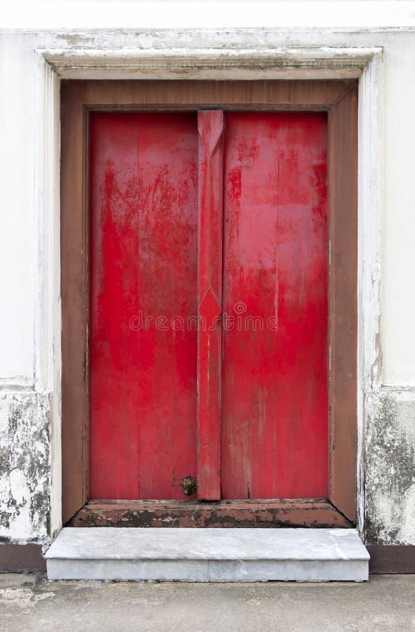 Grande porta di legno rossa La vecchia retro porta d'annata fatta di legno duro fotografia stock libera da diritti