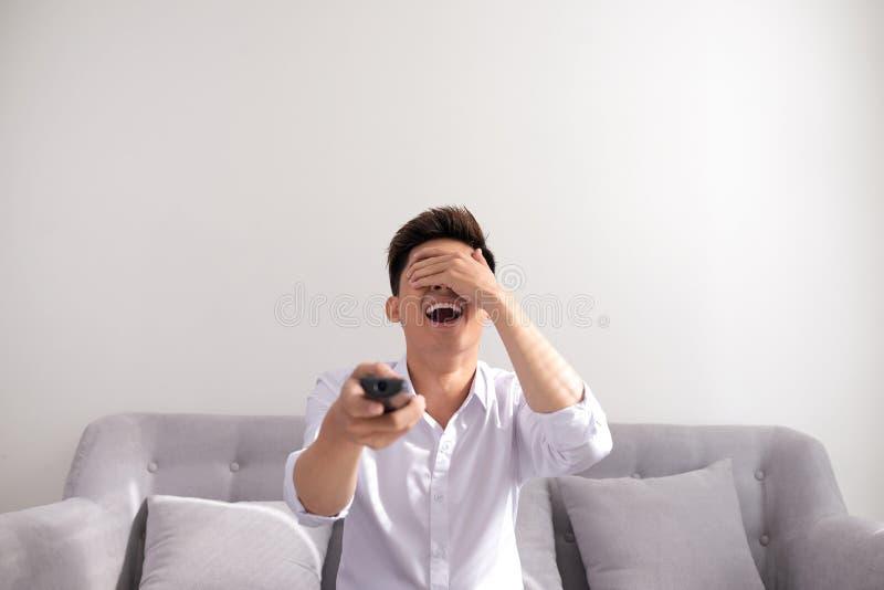 Grande programa televisivo Homem novo alegre consider?vel que guarda a tev? de controle remoto e olhando ao sentar-se no sof? em  imagem de stock