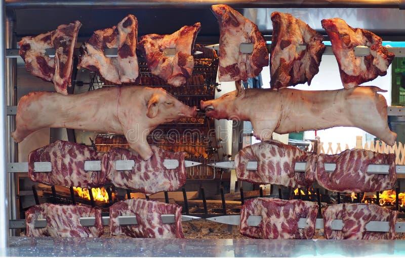 Grande rôtissoire avec plusieurs broches rotatoires avec du porc, les nervures et le quart entiers de boeuf Sur le poulet derrièr image stock