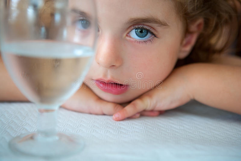 Grande ragazza del bambino degli occhi azzurri che esamina macchina fotografica da una tazza dell'acqua fotografia stock libera da diritti