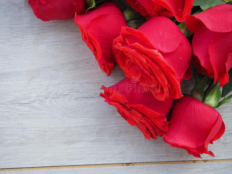 Grande ramalhete das rosas em uma caixa de madeira em um fundo de madeira, para cartão, cumprimentos, espaço para o texto foto de stock