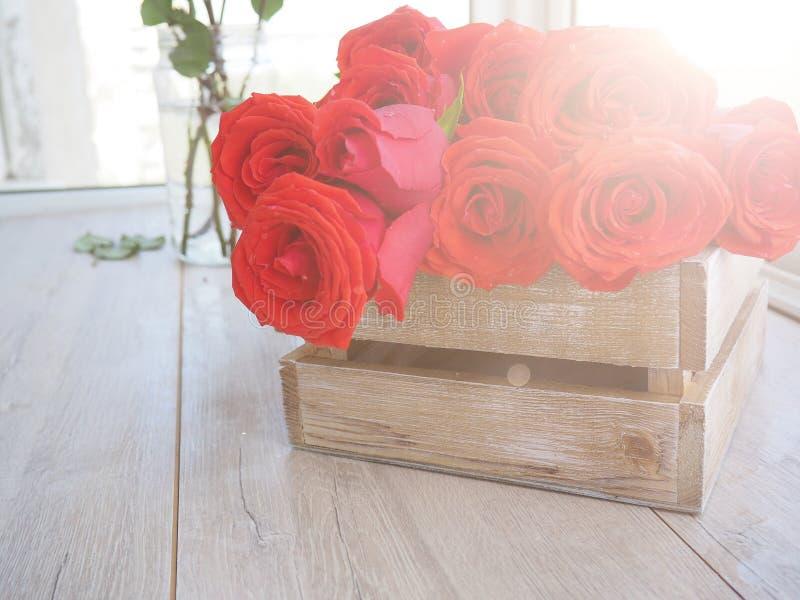 Grande ramalhete das rosas em uma caixa de madeira em um fundo de madeira, para cartão, cumprimentos, espaço para o texto imagem de stock royalty free