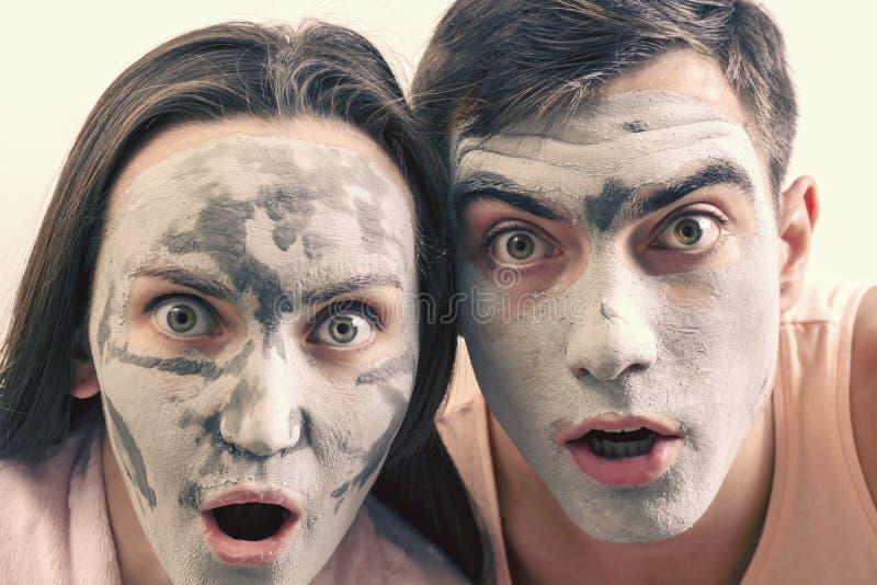 Grande retrato emocional de um casal nas máscaras para a cara da argila termas do dia, bem-estar, skincare foto de stock royalty free