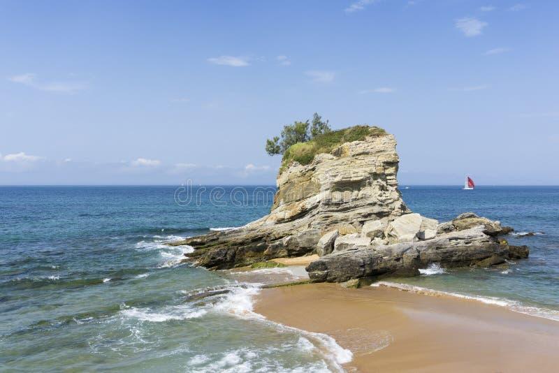Grande roccia all'estremità della spiaggia fotografie stock