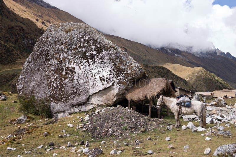 Grande roccia alla traccia di Salcantay con una capanna immagini stock