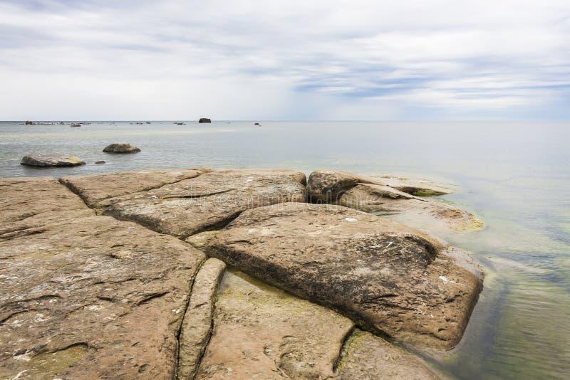 Grande roccia piana marrone nel mare fotografia stock libera da diritti