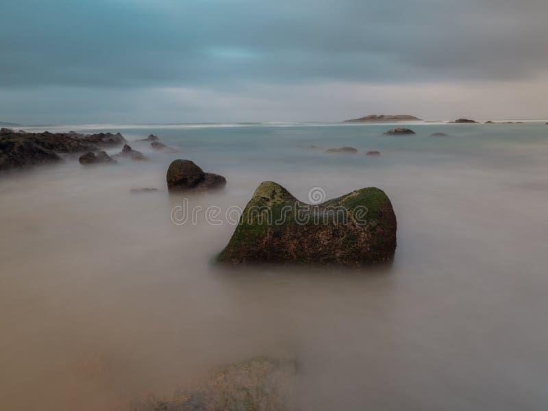 Grande roccia su una spiaggia spagnola con un'isola sui precedenti fotografie stock libere da diritti