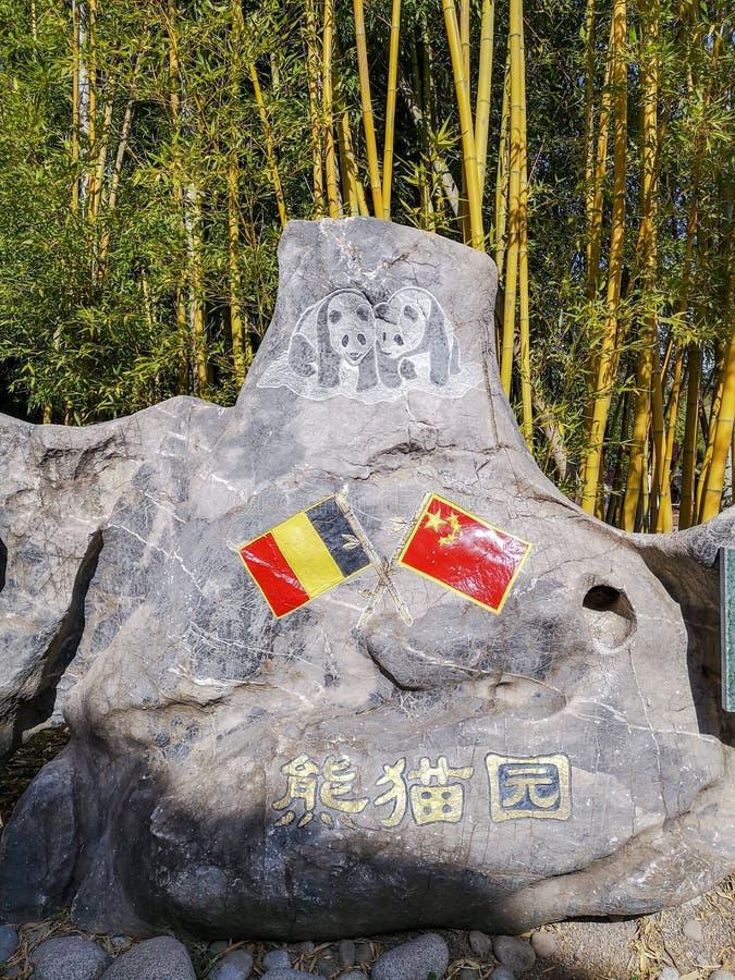 Grande rocha com as bandeiras chinesas e belgas na entrada do complexo da panda gigante em Pairi Daiza imagem de stock