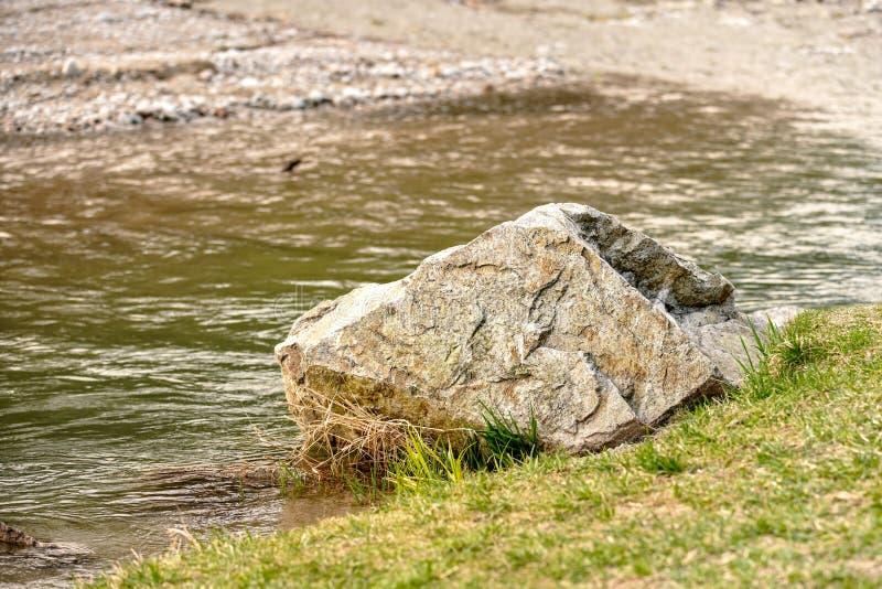 Grande rocha do pedregulho no lado da grama do rio foto de stock