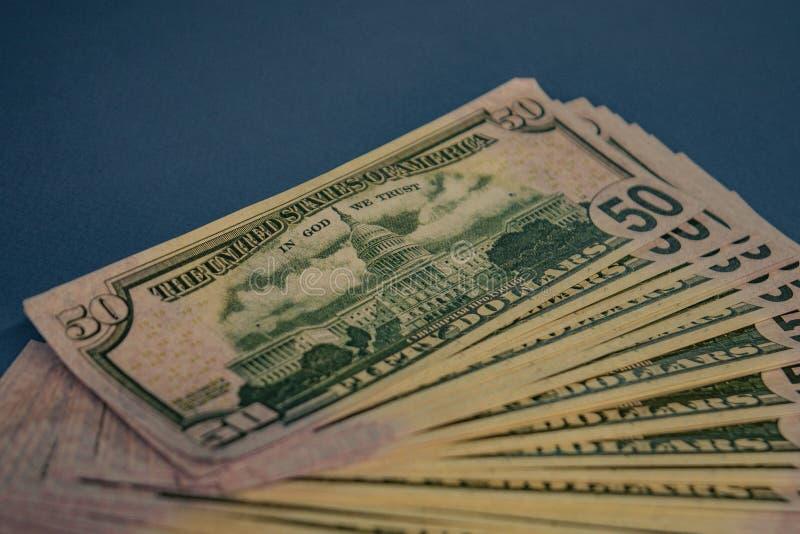Grande rolo gordo do dinheiro em um fundo azul foto de stock