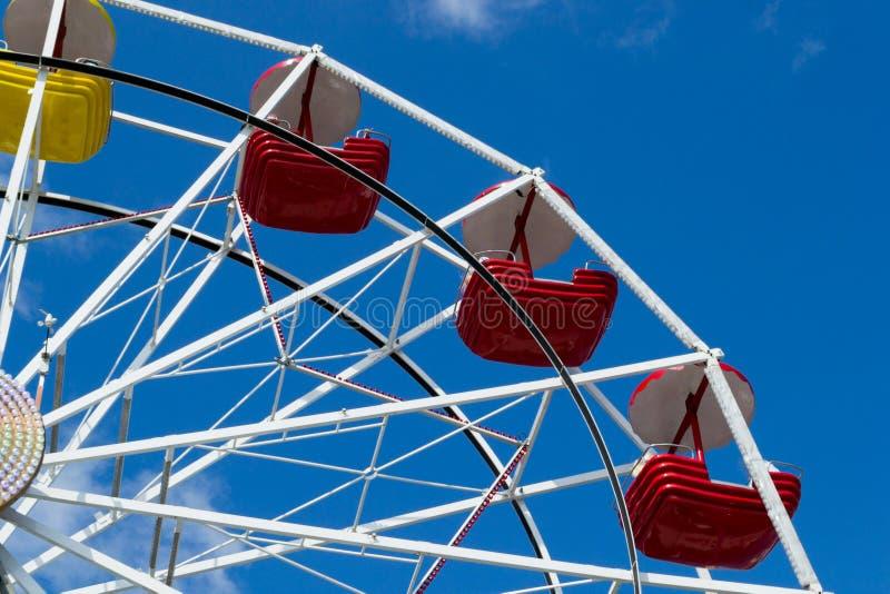 Grande roue avec les cuvettes jaunes et rouges contre le ciel bleu avec les nuages minces photos stock