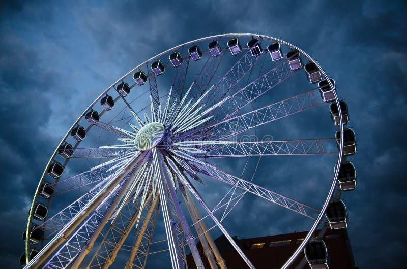 Grande roue de ferris lumineuse devant le ciel dramatique bleu-foncé photos libres de droits