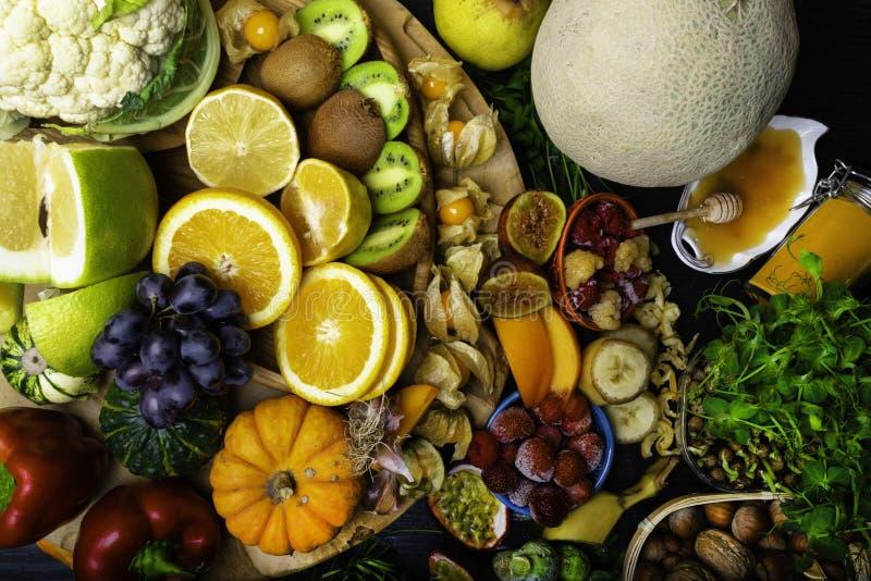 Grande sélection de nourriture biologique avec des nourritures hautes aux antioxydants et à l'arrière-plan noir en bois de vitami photographie stock libre de droits