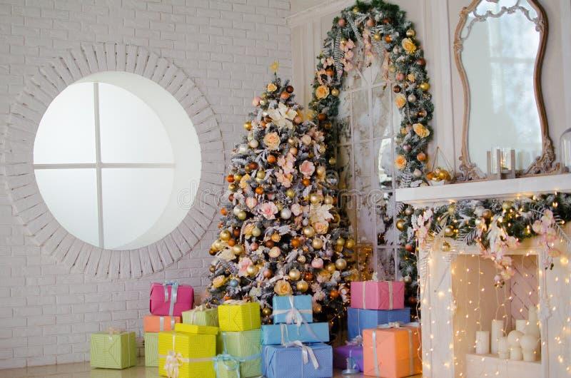 Grande sala branca com a árvore de Natal, os presentes, a chaminé e a janela redonda foto de stock