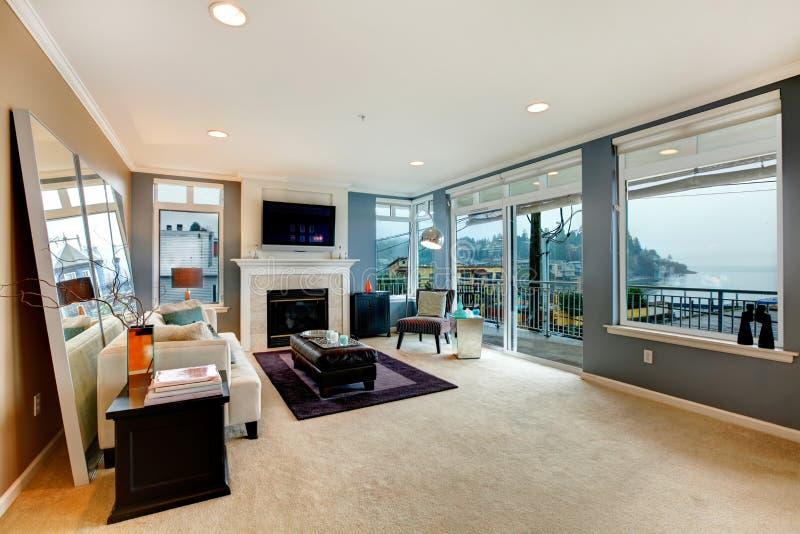 Grande sala de visitas aberta da reentrância com chaminé, tevê e mobília moderna. imagens de stock