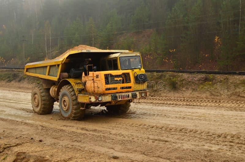 Grande scaricatore diesel giallo della cava sul lavoro Carrello di miniera pesante che trasporta sabbia ed argilla fotografia stock