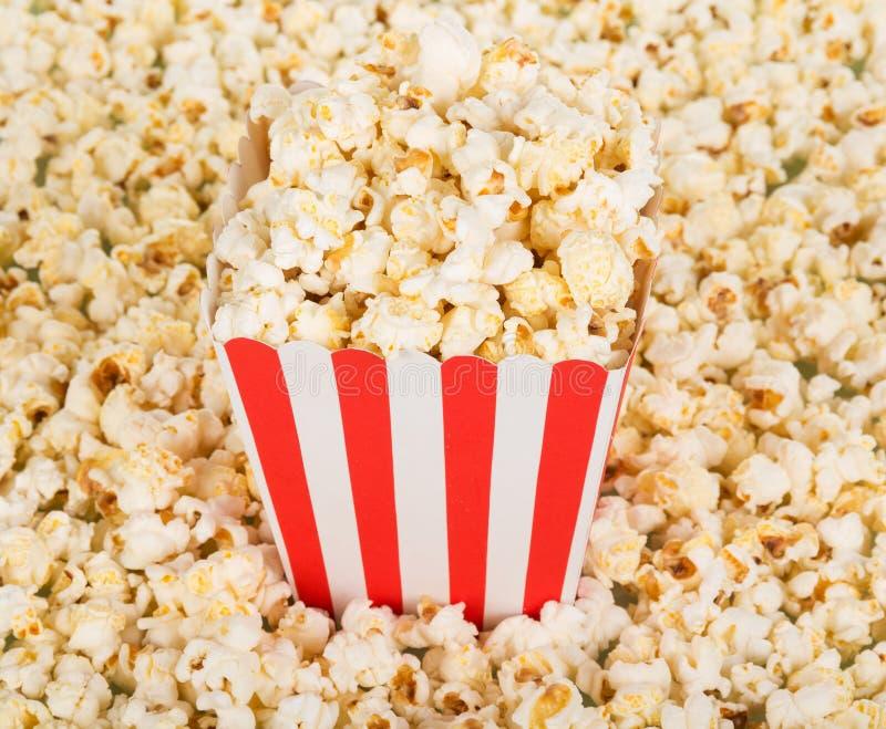 Grande scatola quadrata di popcorn e popcorn del lotto intorno Fondo fotografia stock
