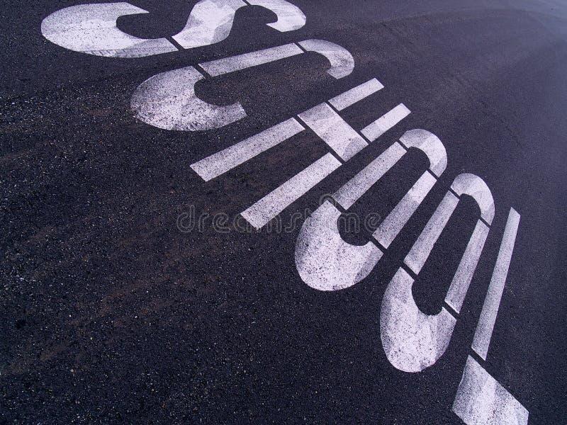 Grande sinal da ESCOLA pintado em uma rua urbana fotografia de stock