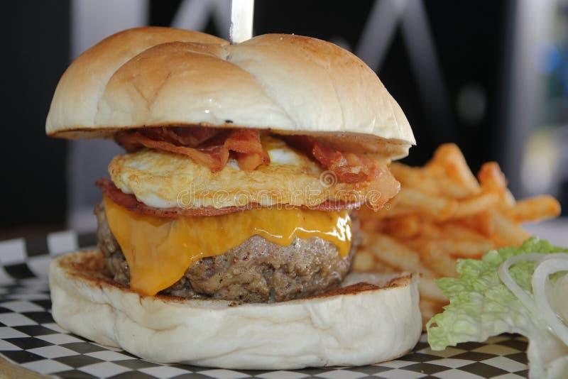 Grande singolo cheeseburger con le patate fritte immagine stock libera da diritti