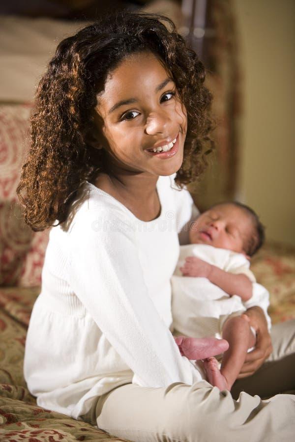 Grande soeur retenant l'enfant de mêmes parents nouveau-né photographie stock libre de droits