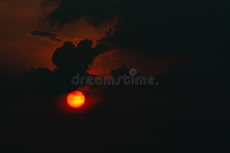 Grande sole rosso in nuvole scure Tramonto del diavolo Vista di orrore del sole in cielo delle nuvole nere Tramonto di estate Sol immagine stock
