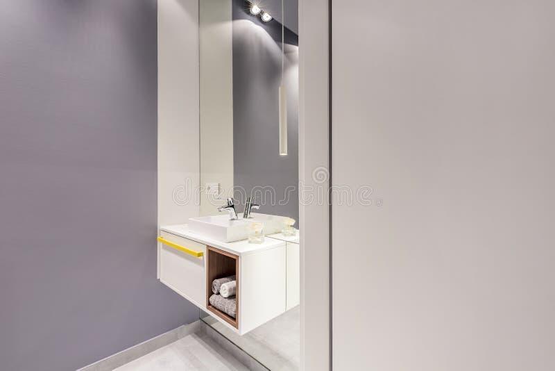 Grande specchio ed armadietto bianco con gli asciugamani e lavandino nell'interno grigio del bagno con le pareti vuote per i vost immagini stock